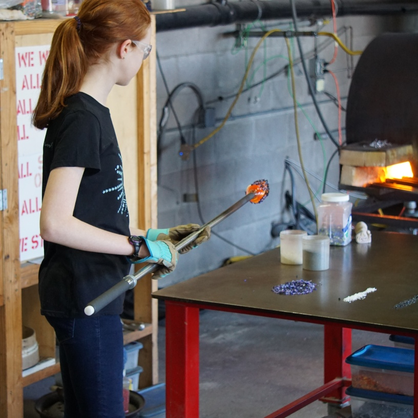 Sienna rolling her hot glass through some colored glass.