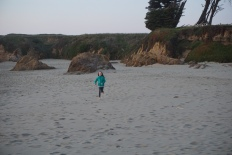 Kie running and enjoying the cold sand.